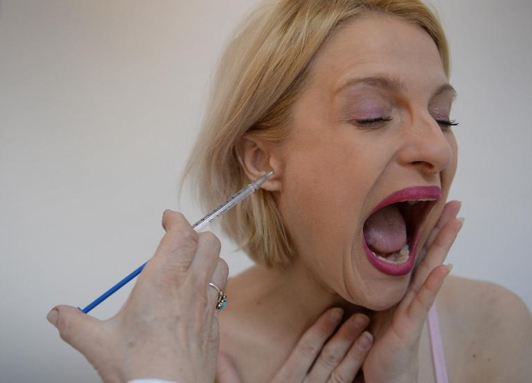 Doina Postolachi, 34, receives bee venom treatment at a medical center in Bucharest, on March 28, 2014