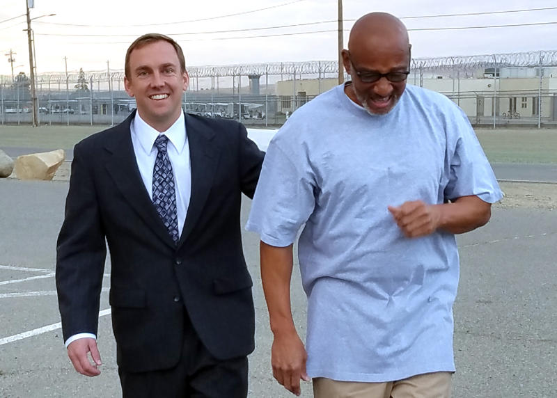 This photo provided by California Innocence Project shows Horace Roberts, right, walking out of Avenal State Prison with California Innocence Project managing attorney Michael Semanchik after being released from Avenal State Prison in Avenal, Calif., Oct. 3, 2018. Roberts, wrongly convicted of murdering his lover two decades ago has been exonerated and new arrests have been made in the case. (California Innocence Project via AP)