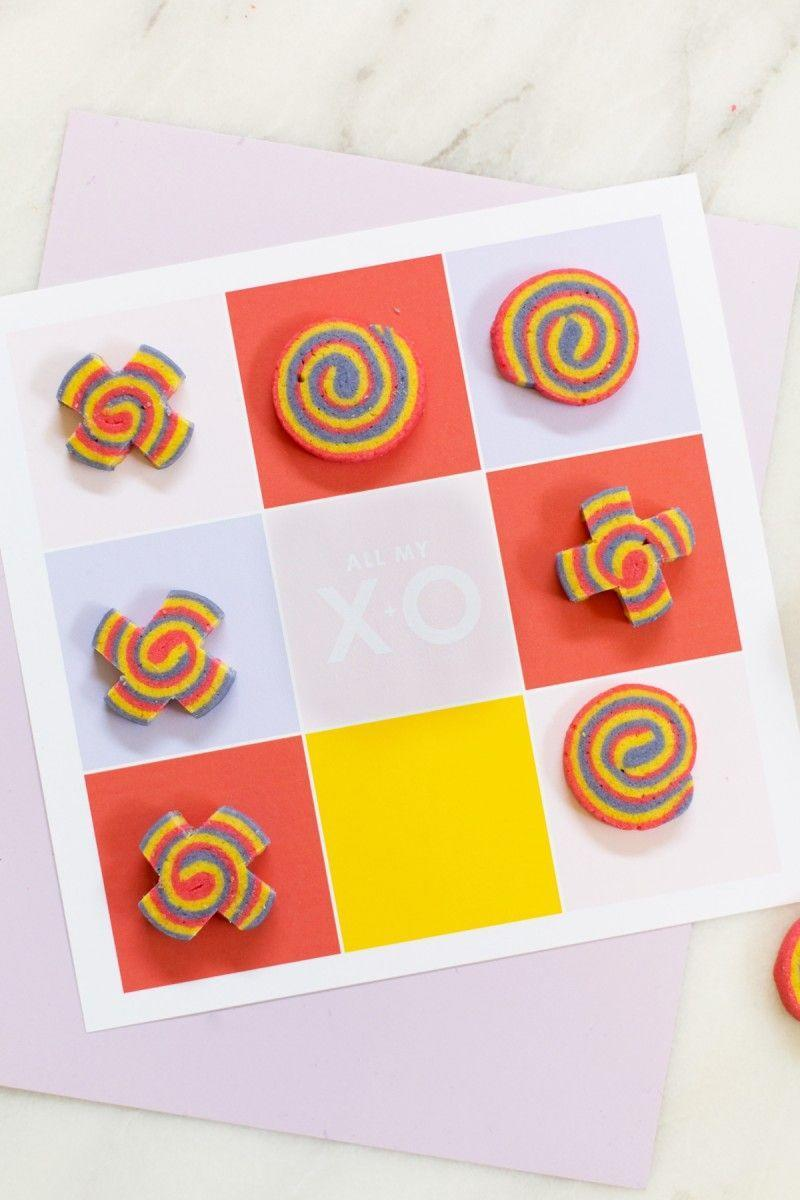 """<p>Create these cute, colorful cookies for a tasty spin on a tic-tac-toe game. In a pinch? Try two different kinds of candy instead (for example, candy hearts and chocolate kisses).</p><p><strong>Get the tutorial at <a href=""""https://lovelyindeed.com/diy-tic-tac-toe-valentine-x-o-cookies/"""" rel=""""nofollow noopener"""" target=""""_blank"""" data-ylk=""""slk:Lovely Indeed"""" class=""""link rapid-noclick-resp"""">Lovely Indeed</a>.</strong></p><p><strong><a class=""""link rapid-noclick-resp"""" href=""""https://www.amazon.com/Neenah-80944-01-Astrobrights-Colored-Cardstock/dp/B01LX0UJBN/?tag=syn-yahoo-20&ascsubtag=%5Bartid%7C10050.g.25916974%5Bsrc%7Cyahoo-us"""" rel=""""nofollow noopener"""" target=""""_blank"""" data-ylk=""""slk:SHOP CARD STOCK"""">SHOP CARD STOCK</a><br></strong></p>"""