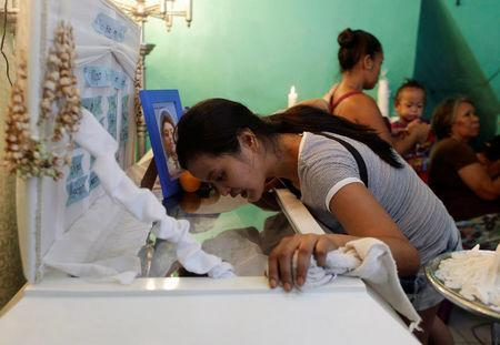 Jennelyn Olaires, 26, looks at the body of her partner Michael Siaron during his wake in Pasay, Metro Manila, Philippines July 28, 2016. REUTERS/Czar Dancel