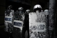 Riot police officers covered by paint thrown by protesters stand guard as activists try to stop the eviction of Axel Altadill, 28 from his apartment in Barcelona, Spain, Tuesday, May 25, 2021. Altadill has been accused of squatting in the apartment since January 2019. (AP Photo/Joan Mateu)