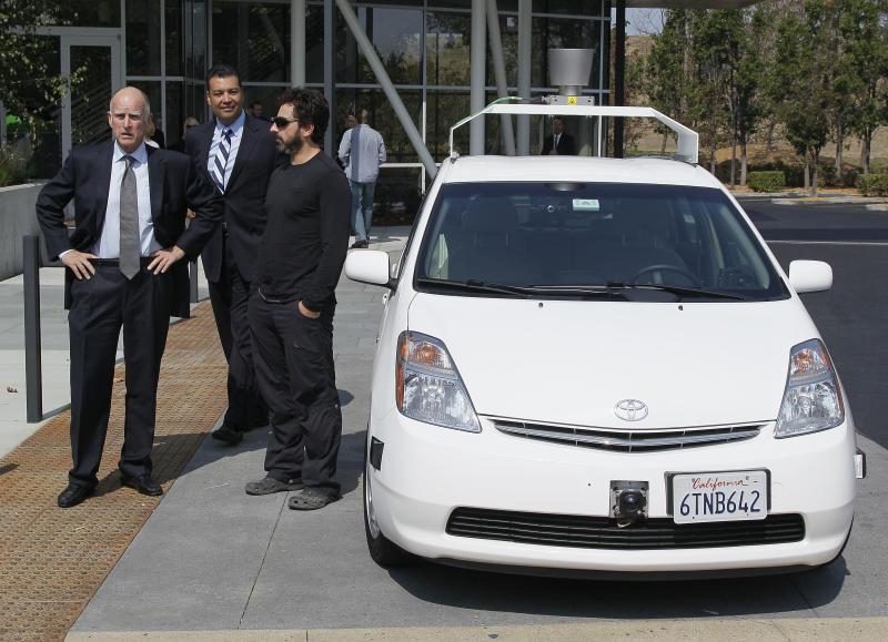 From left, California Gov. Edmund G Brown Jr., state Senator Alex Padilla and Google co-founder Sergey Brin stand by a driverless car they arrived in at Google headquarters in Mountain View, Calif., Tuesday, Sept. 25, 2012. Brown visited Google to sign legislation for driverless cars. The legislation will open the way for driverless cars in the state. Google, which has been developing autonomous car technology and lobbying for the legislation has a fleet of driverless cars that has logged more than 300,000 miles (482,780 kilometers) of self-driving on California roads. (AP Photo/Eric Risberg)