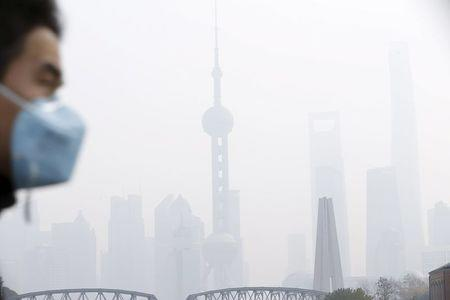 A man wearing a face mask walks on a bridge in front of the financial district of Pudong amid heavy smog in Shanghai, China, December 15, 2015. REUTERS/Aly Song