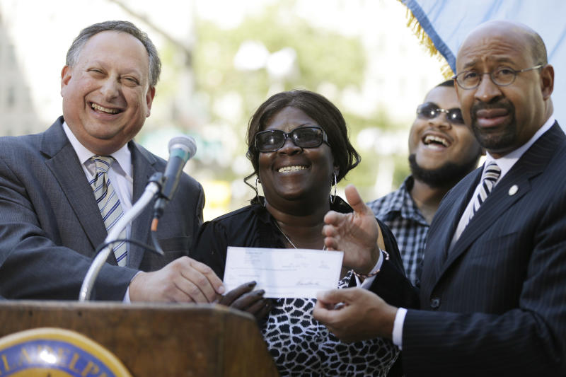 Jeffrey M. Snyder, left, with Xfinity Live which donated $25,000 for a statue of Joe Frazier, poses for photographs with Frazier's daughter Renae Frazier-Martin, son Brandon Frazier, and Philadelphia Mayor Michael Nutter, outside of City Hall during a news conference, Wednesday, Sept. 12, 2012, in Philadelphia. The statue is expected to be placed at Xfinity Live, an entertainment complex near Philadelphia's three sports stadiums. (AP Photo/Matt Rourke)