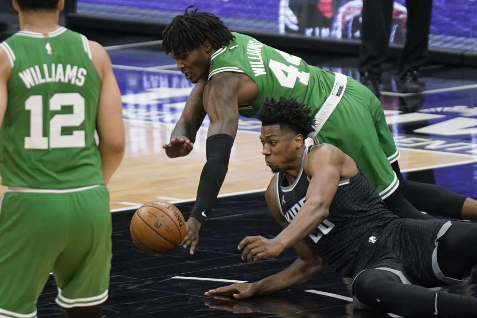 Sacramento Kings center Hassan Whiteside, right, and Boston Celtics center Robert Williams III, background, dive for the ball during the second half of an NBA basketball game in Sacramento, Calif., Wednesday, Feb. 3, 2021. The Kings won 116-111. (AP Photo/Rich Pedroncelli)