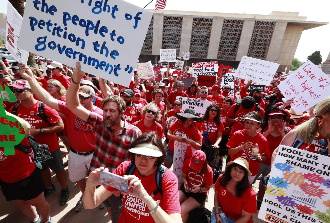 <p>Teachers rally outside the Capitol on Monday, April 30, 2018, in Phoenix on their third day of walk outs. Teachers in Arizona and Colorado walked out of their classes over low salaries keeping hundreds of thousands of students out of school. It's the latest in a series of strikes across the nation over low teacher pay. (Photo: Matt York/AP) </p>