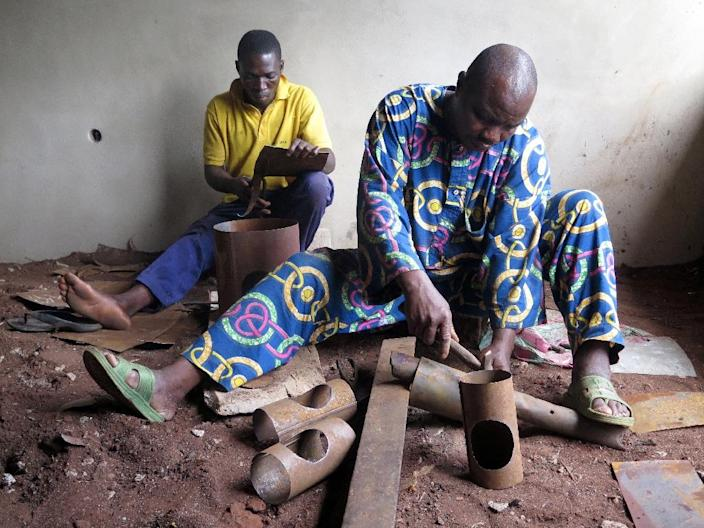 Workers make solar-powered cookers at a factory in Akpro-Misserete, outside of Porto-Novo on October 1, 2015 (AFP Photo/)