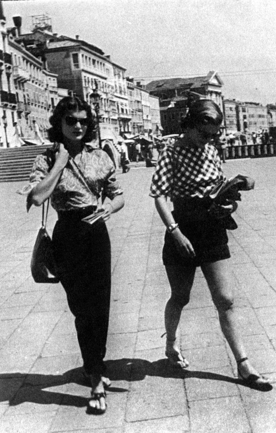 <p>Sisters Jacqueline and Caroline Lee Bouvier play the part of chic locals while traveling in Venice. Jackie wears a paisley-printed blouse with black paper-bag pants. <br></p>