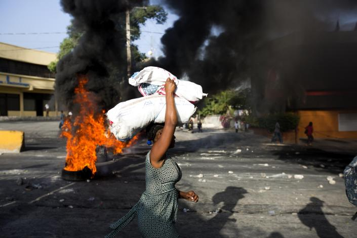 <p>A woman carries items during a protest over the cost of fuel in Port-au-Prince, Haiti, Saturday, July 7, 2018. (Photo: Dieu Nalio Chery/AP) </p>