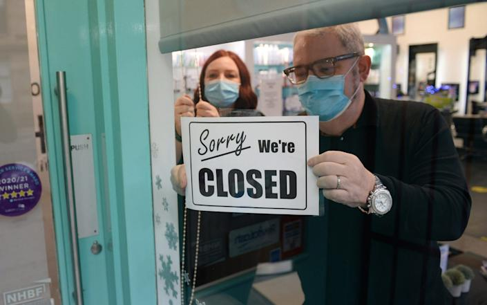 Ken Main at Ellen Conlin Hair and Beauty gets his business ready for lockdown as Scotland's non essential shops and close contact businesses close for three weeks - James Chapelard