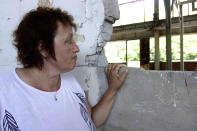 Devla Ajsic looks through the ruins of a former battery factory in Potocari near Srebrenica, Bosnia, Wednesday, July 7, 2021. Ajsic, who fled Srebrenica after being sexually abused in July 1995, has returned to live there, but says she is still afraid to walk through the town because she never knows if the people she encounters in the streets are genocide deniers or even took part in it. (AP Photo/Eldar Emric)