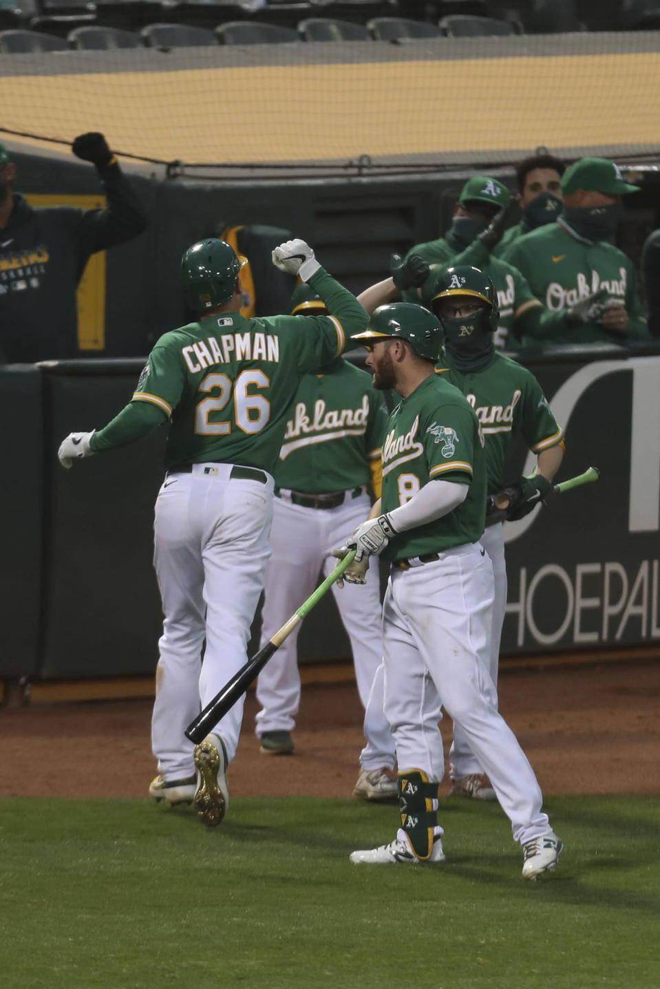 Oakland Athletics Matt Chapman is congratulated after hitting a solo home run against the Texas Rangers during the seventh inning of a baseball game in Oakland, Calif., Tuesday, Aug. 4, 2020. (AP Photo/Jed Jacobsohn)