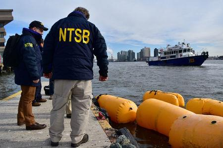 U.S. National Transportation Safety Board (NTSB) Go Team gathers information on scene while awaiting salvage of the helicopter that crashed in the East River in New York, U.S., in this image released on March 12, 2018.   NTSB/Handout via REUTERS