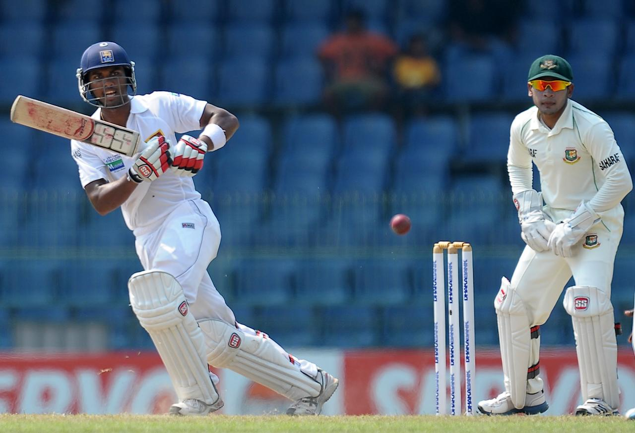 Sri Lanka's cricketer Dinesh Chandimal (L) plays a shot as Bangladeshi wicketkeeper and captain Mushfiqur Rahim looks on during the second day of their second Test match between Sri Lanka and Bangladesh at the R. Premadasa Cricket Stadium in Colombo on March 17, 2013. AFP PHOTO/ LAKRUWAN WANNIARACHCHI