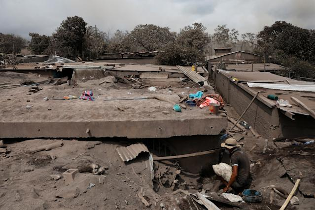 <p>Alejandro Esqueque, 45, looks for the remains of his mother and nephews at his home, in the area affected by the eruption of the Fuego volcano at San Miguel Los Lotes in Escuintla, Guatemala, June 6, 2018. REUTERS/Carlos Jasso – RC1485C03000 </p>