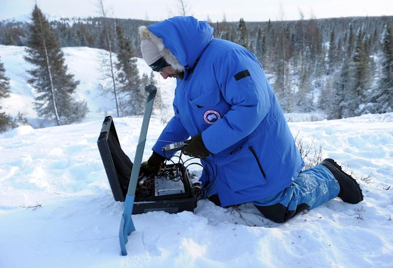 French biologist and leading scientist at Takuvik Joint International Laboratory sets up equipment to detect temperature changes in the tundra near Kuujjuarapik, Quebec, Canada on December 5, 2014 (AFP Photo/Clement Sabourin)
