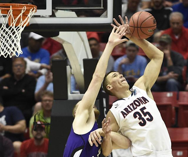 Arizona center Kaleb Tarczewski battles with Weber State center Kyle Tresnak for a rebound during the first half in a second-round game in the NCAA college basketball tournament Friday, March 21, 2014, in San Diego. (AP Photo/Denis Poroy)