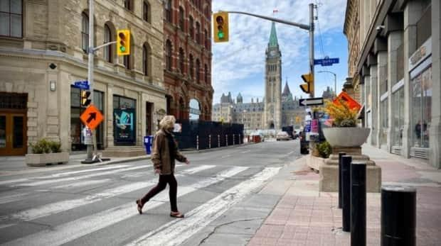 A pedestrian wearing a mask crosses Metcalfe Street in downtown Ottawa on April 27, 2021. (Christian Patry/Radio-Canada - image credit)
