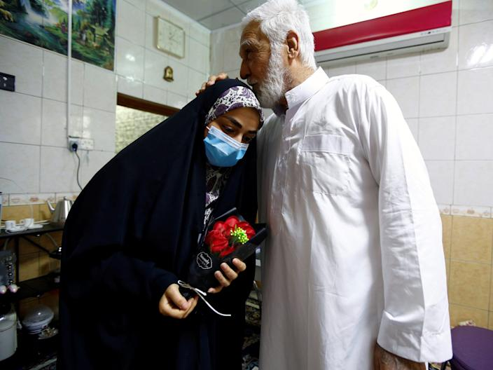 Farah Al-Awadi, a 28-year-old Iraqi woman who left quarantine after her recovery from COVID-19, wears a protective mask while her father kisses her at her home in Najaf, Iraq, April 1, 2020.