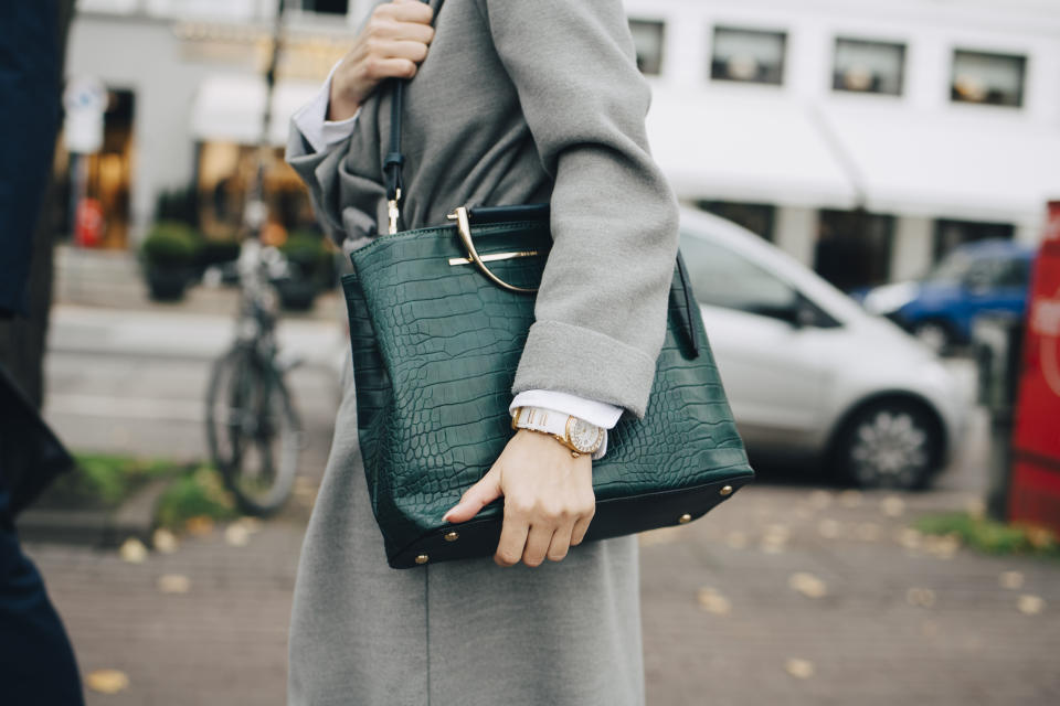 Woman holding green shoulder bag while walking outdoors. (Getty Images/Maskot)