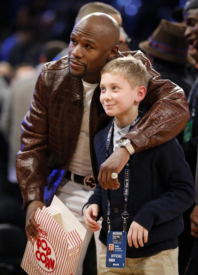 Boxer Floyd Mayweather Jr. poses for a photograph with a fan during the first half of the NBA All-Star basketball game, Sunday, Feb. 15, 2015, in New York. (AP Photo/Kathy Willens)