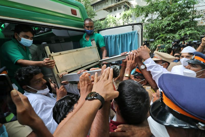 People load the body of Bollywood actor Dilip Kumar into an ambulance for his funeral in Mumbai