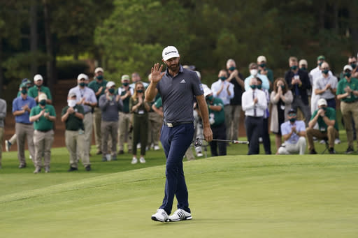 FILE - Dustin Johnson waves after winning the Masters golf tournament in Augusta, Ga., in a Sunday, Nov. 15, 2020, file photo. Some volume is returning to the Masters, just maybe not the head-turning roars. Augusta National Chairman Fred Ridley said Tuesday, Jan. 12, 2021, the club intends to allow a limited number of spectators for the Masters on April 8-11, provided it can be done safely, given the coronavirus pandemic. (AP Photo/David J. Phillip, File)