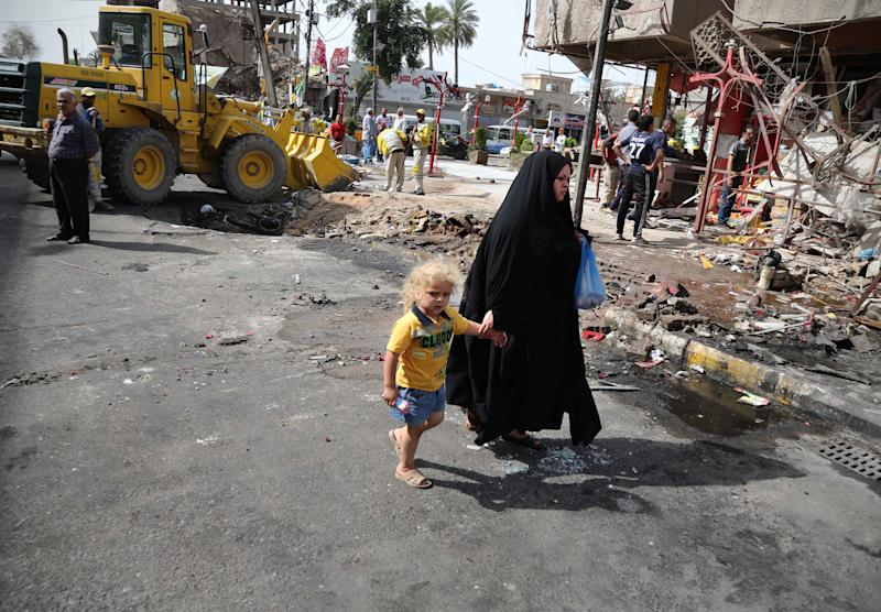 A woman walks with her child through the aftermath of a car bomb attack in the crowded commercial area of Karrada, in Baghdad, Iraq, Friday, April 18, 2014. Authorities in Iraq say a car bomb targeted a street full of shoppers in the capital. in Baghdad on Thursday,AP Photo/Karim Kadim)