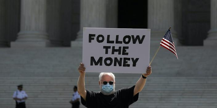 """Demonstrator Bill Christeson holds a sign reading """"follow the money"""" as the U.S. Supreme Court ruled that a prosecutor in New York City can obtain President Donald Trump's financial records including tax returns, moments before the ruling outside the court in Washington, DC, July 9, 2020."""