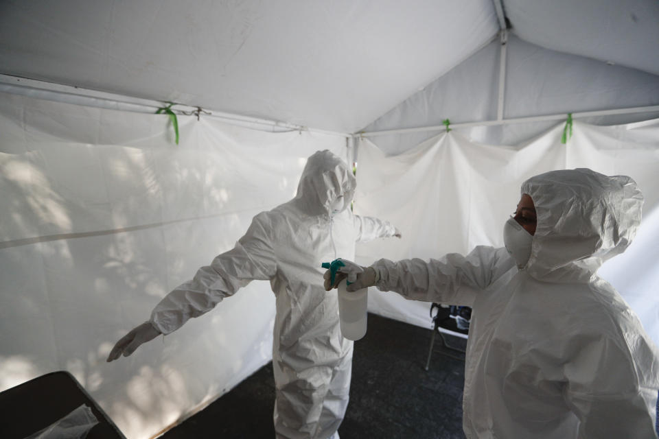 A healthcare worker disinfects a colleague at the end of a day of collecting sample to test for the new coronavirus inside a mobile diagnostic tent, in the Coyoacan district of Mexico City, Friday, Nov. 13, 2020. Mexico City announced Friday it will order bars closed for two weeks after the number of people hospitalized for COVID-19 rose to levels not seen since August. (AP Photo/Eduardo Verdugo)