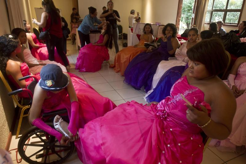 "Yamileth Barrera, left, a 16-year-old from San Jose de Bocay, on a wheelchair she uses because of bone cancer. ties the shoe of her friend Keyling Kenry, suffering from a Hodgkin's lymphoma, as they prepare for a ""quinceanera"" party in Managua, Nicaragua, Saturday Sept. 21, 2013. For each of the past five years, Nicaragua's Association of Mothers and Fathers of Children with Cancer and Leukemia has put on a ""quinceanera"" party for girls from poor, rural families, teens who have the added burden of dealing with cancer. This year's party feted 37 girls between ages 14 and 16 on Saturday night at a hotel in Nicaragua's capital.(AP Photo/Esteban Felix)"