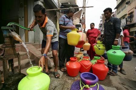 Man uses a hand-pump to fill up a container with drinking water as others wait in a queue on a street in Chennai