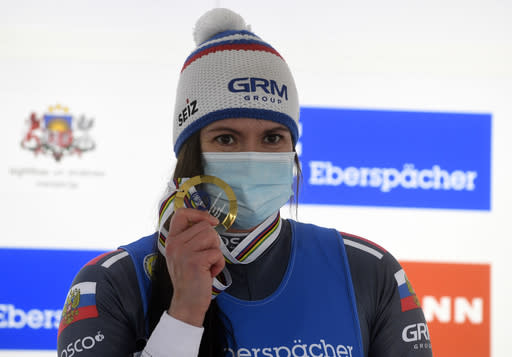 Tatyana Ivanova of Russia wearing a face mask to protect against coronavirus celebrates on the podium after finishing first of a women's race at the Luge World Cup event in Sigulda, Latvia, Sunday, Jan. 10, 2021. (AP Photo/Roman Koksarov)