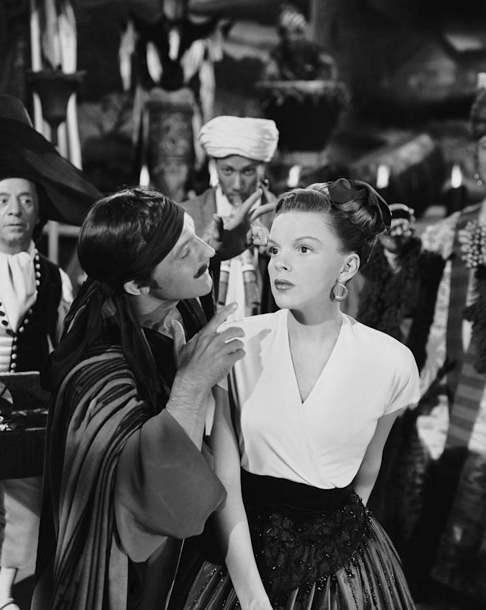 """<p>After getting hooked on the """"pep pills"""" MGM was giving her, Judy Garland struggled with addiction. She called in sick 16 days while working on <em>Meet Me in St. Louis, </em>and production on <em>The Pirate </em>was delayed by the actress. All filming delays due to her absence <a href=""""https://timeline.com/hollywood-drugs-1930s-6b27a1404552"""" rel=""""nofollow noopener"""" target=""""_blank"""" data-ylk=""""slk:came out of her paycheck"""" class=""""link rapid-noclick-resp"""">came out of her paycheck</a>, which at one point reached $100,000.</p>"""