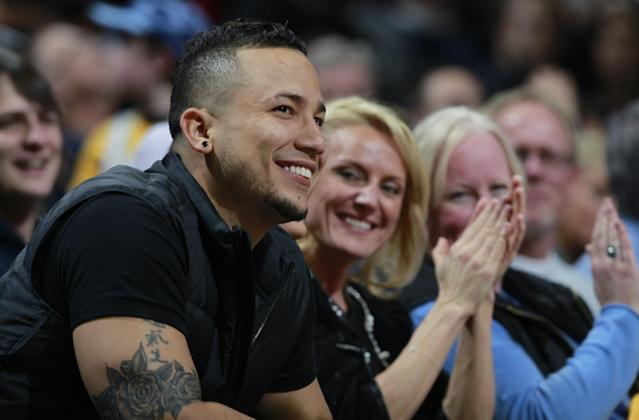 Colorado Rockies outfielder Carlos Gonzalez smiles as the crowd applauds as he is introduced in the fourth quarter while sitting court side to watch the Miami Heat's 97-94 victory over the Denver Nuggets in an NBA basketball game in Denver on Monday, Dec. 30, 2013. (AP Photo/David Zalubowski)