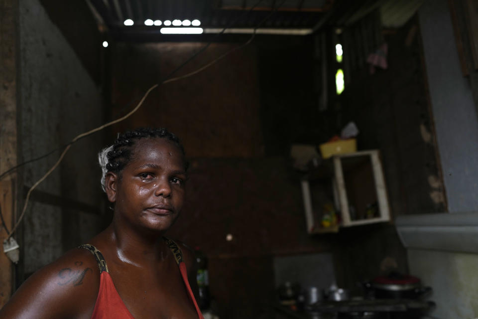 Francielle de Santana cries as she explains that some days her family doesn't have food to eat, at their home in the Jardim Gramacho favela of Rio de Janeiro, Brazil, Monday, Oct. 4, 2021. Surging inflation on food and electricity are affecting the poor, with rising gas prices forcing some to cook with firewood and alcohol. (AP Photo/Silvia Izquierdo)