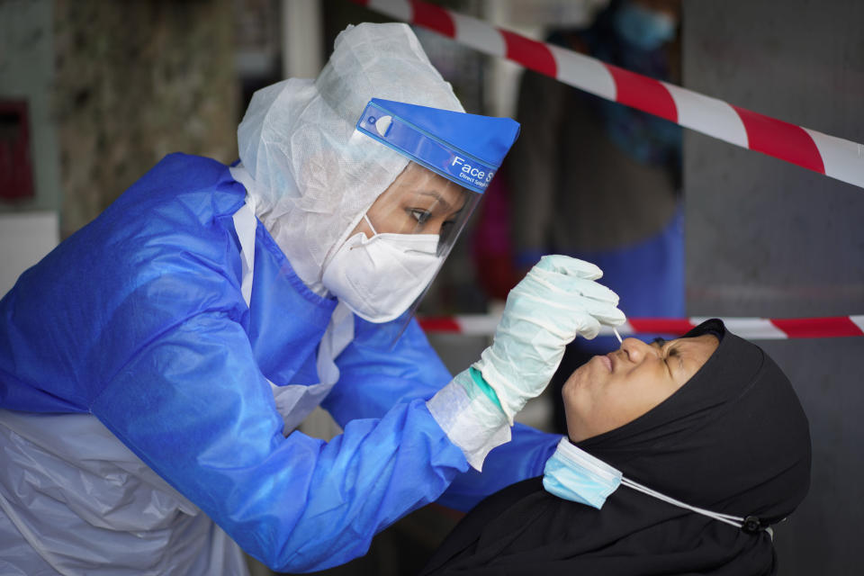 A doctor collects a sample for a coronavirus test at a clinic in Puchong on the outskirts of Kuala Lumpur, Malaysia, Tuesday, Oct. 6, 2020. Virus cases in Malaysia spiked to a new daily record high of 691 on Tuesday, with four new deaths including a one-year-old baby. Prime Minister Muhyiddin Yassin said there will not be another national lockdown as this will crush the economy, but measures will be targeted to curb transmission in hotspot zones. (AP Photo/Vincent Thian)