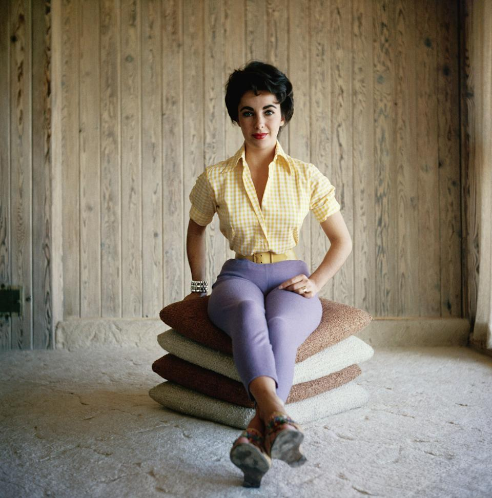 Actress Elizabeth Taylor sits on a stack of pillows, wearing purple pants and a yellow shirt in this undated photo.