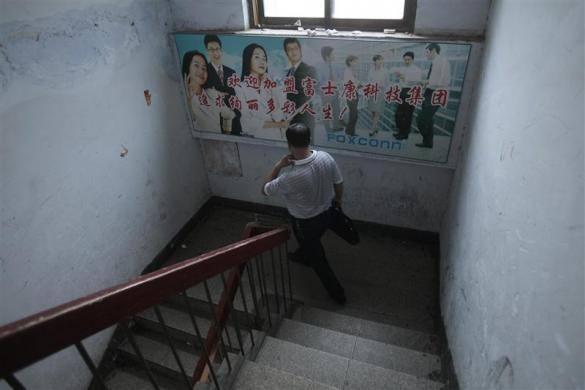 "A job seeker walks down stairs at a recruitment centre, past a poster on the wall which reads ""Welcome to Foxconn, Join Us For a Better Living"", in Zhengzhou, Henan province in central China August 11, 2010."