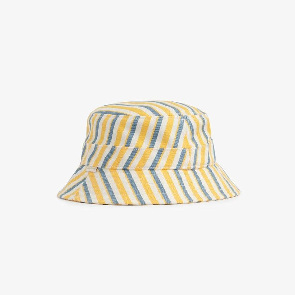 """Dua Lipa, Rihanna, and Hailey Bieber are all behind the latest re-up of bucket hats in fashion. Join them, why don't you? <br> <br> <strong>Aimé Leon Dore</strong> Striped Cotton Bucket Hat, $, available at <a href=""""https://go.skimresources.com/?id=30283X879131&url=https%3A%2F%2Fwww.aimeleondore.com%2Fcollections%2Fheadwear%2Fproducts%2Fstriped-bucket-hat%3Fvariant%3D31825524195425"""" rel=""""nofollow noopener"""" target=""""_blank"""" data-ylk=""""slk:Aimé Leon Dore"""" class=""""link rapid-noclick-resp"""">Aimé Leon Dore</a>"""