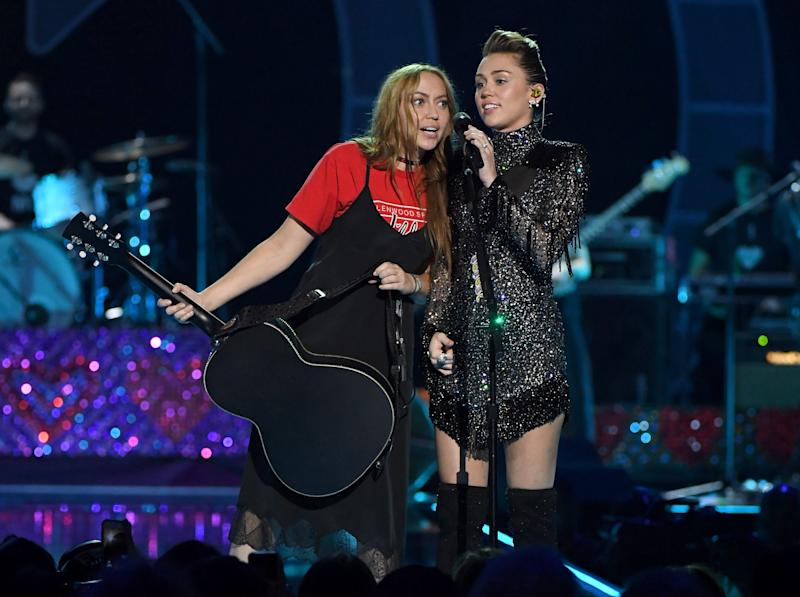 LAS VEGAS, NV - SEPTEMBER 23: Brandi Cyrus (L) gives her sister Miley Cyrus a guitar as she performs during the 2017 iHeartRadio Music Festival at T-Mobile Arena on September 23, 2017 in Las Vegas, Nevada. (Photo by Ethan Miller/WireImage)