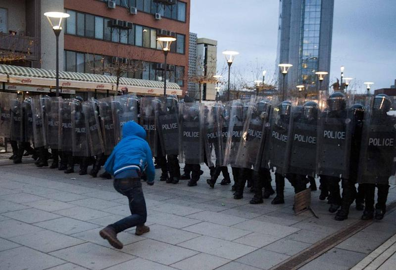 A protestor throws a rock towards riot police in Pristina, Kosovo on January 24, 2015 (AFP Photo/Armend Nimani)