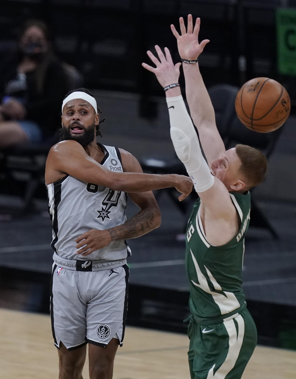 San Antonio Spurs guard Patty Mills, left, passes the ball over Milwaukee Bucks guard Donte DiVincenzo (0) during the second half of an NBA basketball game in San Antonio, Monday, May 10, 2021. (AP Photo/Eric Gay)