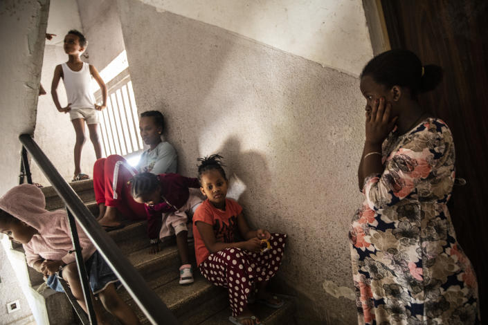Nine month pregnant Eritrean asylum seeker Alganesh Fesahye sit with her children as they take shelter in the stairwell outside their apartment in Ashdod, Israel during a siren warning of rockets fired from Gaza Strip, Tuesday, May 18,2021. (AP Photo/Heidi Levine)