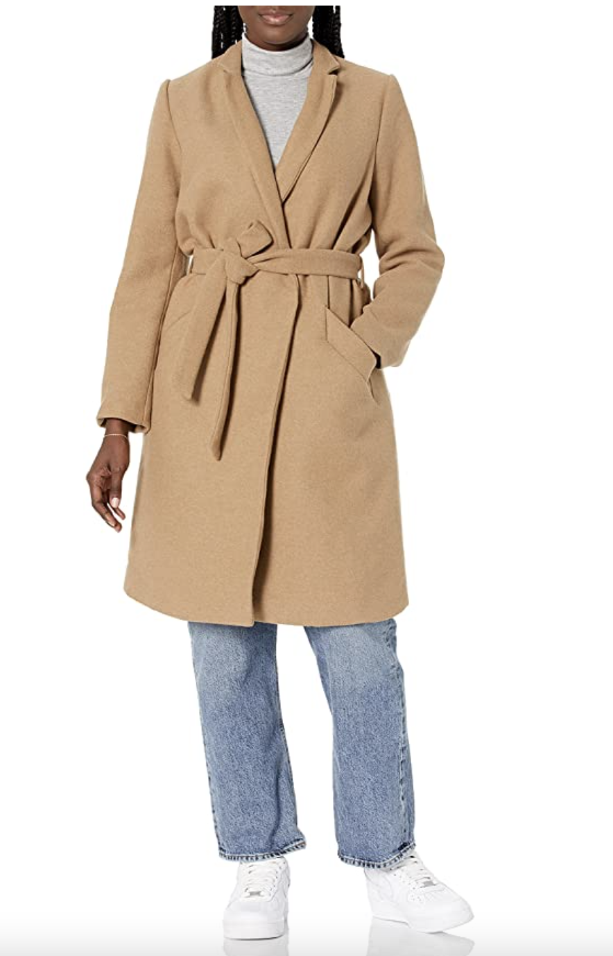 model wearing grey turtleneck, jeans, white sneakers, and Daily Ritual Wool Blend Belted Coat in beige
