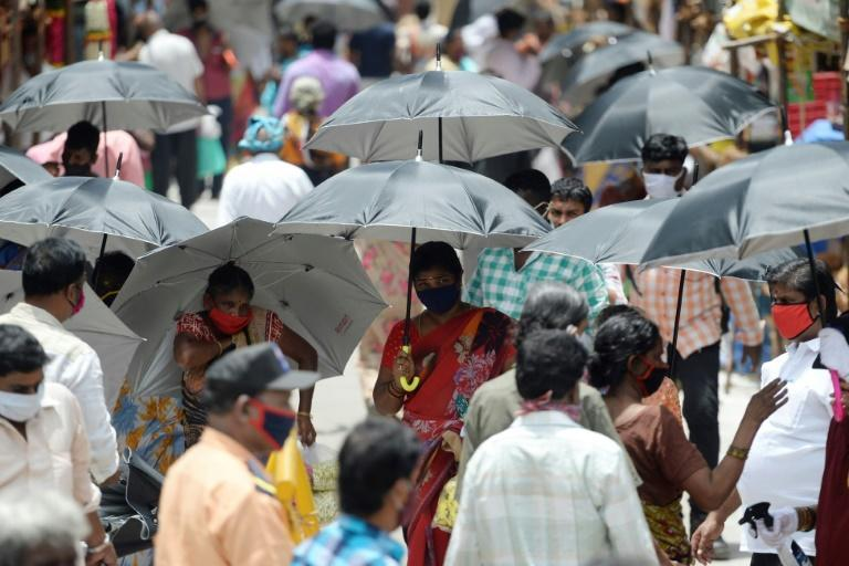 In the Indian city of Chennai, umbrellas have been distributed by volunteers to encourage social distancing (AFP Photo/Arun SANKAR )