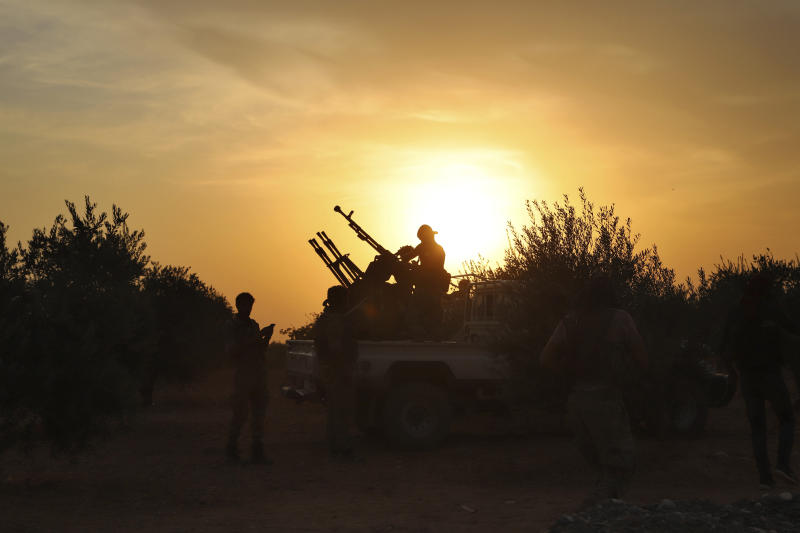 In this Monday, Oct. 14, 2019 photo, Turkey-backed Syrian opposition fighters prepare their guns in Syria's northern region of Manbij. Syrian state media said Tuesday that government forces have entered the center of the once Kurdish-held northern town of Manbij and raised the national flag. (AP Photo)