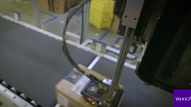 An Amazon fulfillment center SLAM machine scans item and applies a shipping label as part of the final quality-assurance check. Source: Yahoo Finance