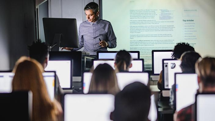 Male teacher giving a lecture from desktop PC during a class at computer lab.