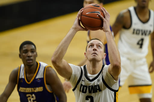 Iowa forward Jack Nunge drives to the basket ahead of Western Illinois guard Marcus Watson Jr., left, during the second half of an NCAA college basketball game, Thursday, Dec. 3, 2020, in Iowa City, Iowa. (AP Photo/Charlie Neibergall)